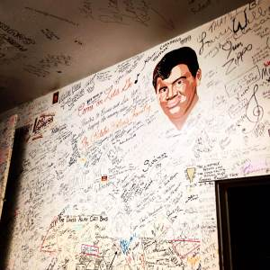 A portrait of Ritchie Valens looks over the