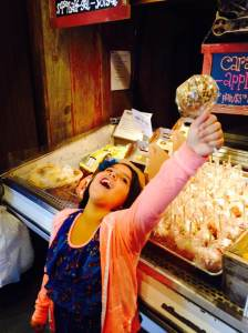 Like pulling the sword from the stone, Leah proudly displays her Wilson's Orchard caramel apple with peanuts!