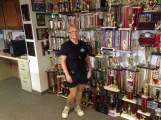 """Kathy Septer shows """"a few"""" of the trophies that the Hills FD has displayed. Her garage at home is jam packed too! Kathy has been participating in Waterball fights since 1985 and still has her eye on the state title."""