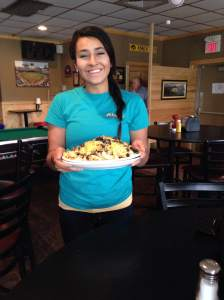 Busting out of the kitchen with our mountainous  appetizer is Ashley. That plate is hot and heavy from the portions Sneakers dishes out.