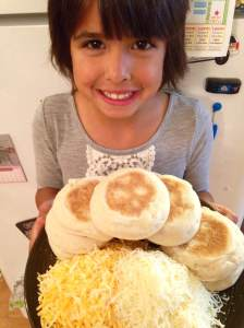 We're preparing serving sized pizzas tonight! Gigi holding up sliced English muffins and a mound of shredded cheese.